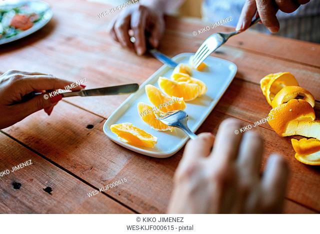 Hands of two persons eating orange slices with cutlery