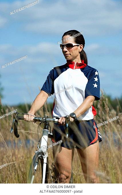 Woman with road bike in nature, portrait