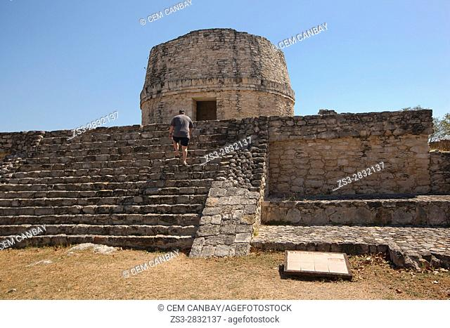 Tourist climbing up the stairs to the Templo Redondo-Round Temple in Mayapan Archeological site, Merida, Yucatan State, Mexico, Central America