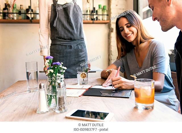 Young woman signing bill at cocktail bar table
