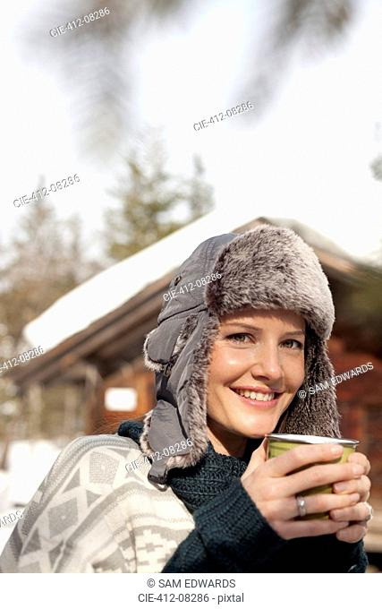 Close up portrait of woman in fur hat drinking coffee outside cabin