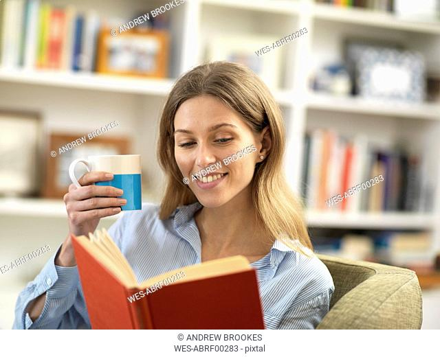 Smiling young woman with a hot drink relaxing at home reading a book