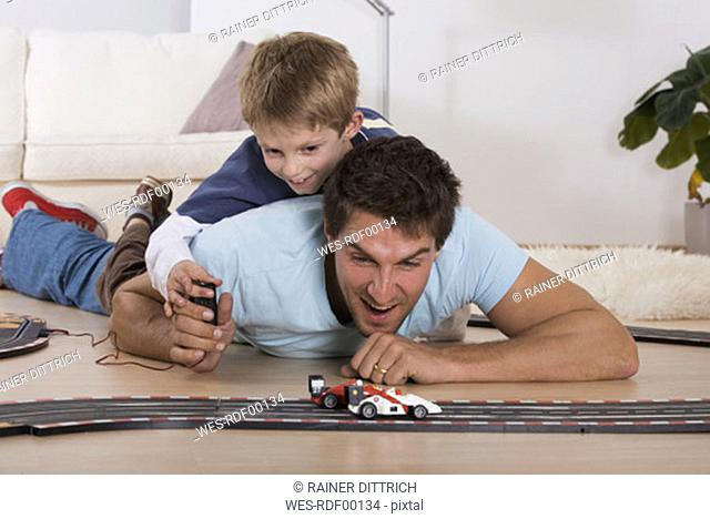 Father and son playing with toy cars