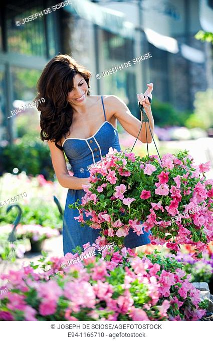 32 year old brunette woman in summer dress holding a hanging container of pink petunias at an outdoors garden market