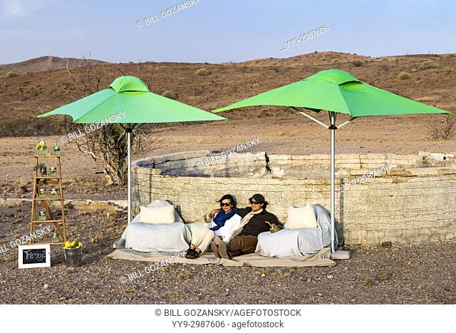 Couple relaxing at Lemonade Stand at Huab Under Canvas, Damaraland, Namibia, Africa