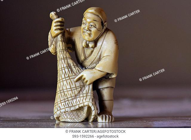 A close up of a small ivory figure of a fisherman and his net