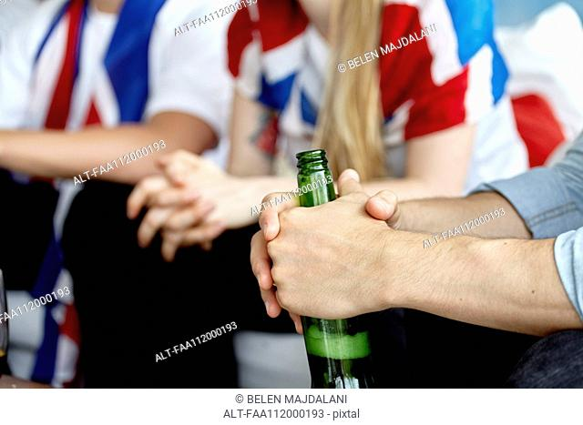 Close-up of sports enthusiast holding bottle of beer in hands