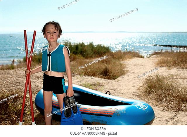 Boy with canoe and fins on beach