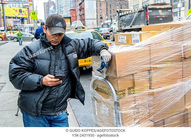 New York, USA. Male delivery guy leaning on a pallet of boxes, while using his smartphone