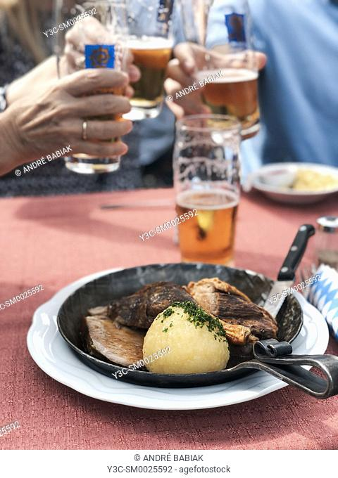 Traditional Bavarian dish with potato dumpling, pork roast, duck roast, in a pan with people clinging beer mugs in the background