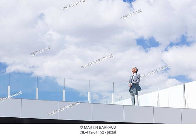 Pensive businessman looking up at sky on rooftop balcony