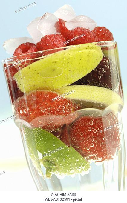 Fruits in glass of water, close-up