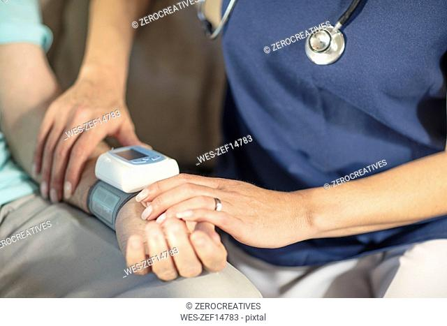 Nurse taking blood pressure of senior patient at home
