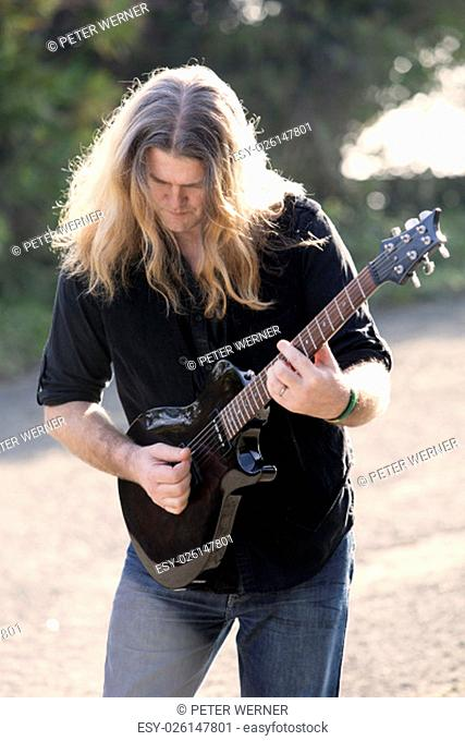 long-haired man playing guitar on the street