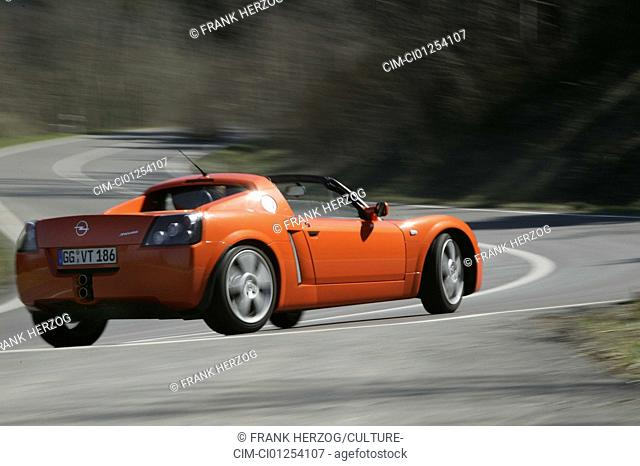Car, Opel Speedster, model year 1999-, Convertible, open top, orange , driving, race track, test track, diagonal from the back, side view