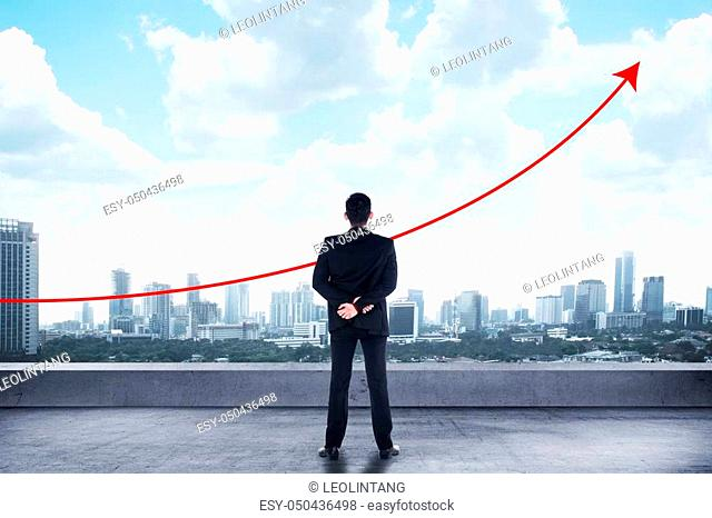 Asian man standing looking the city watching the graph raise