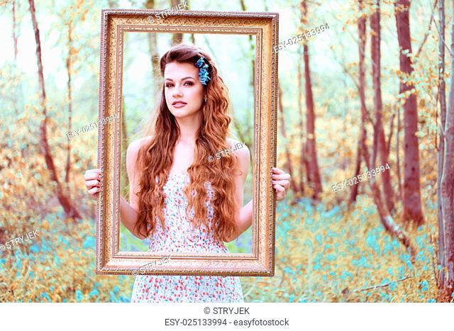 Ravishing woman looking through a portrait frame