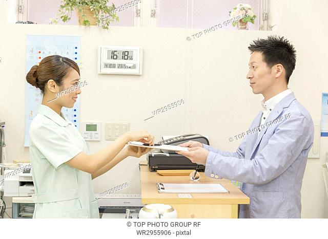 Nurse Passing First-visit Form to the Patient at Receiption Counter