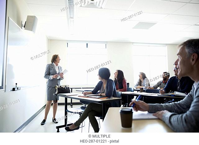 Professor at whiteboard teaching adult education students in classroom