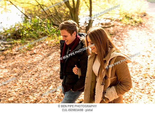 Young couple walking in park, arm in arm, smiling
