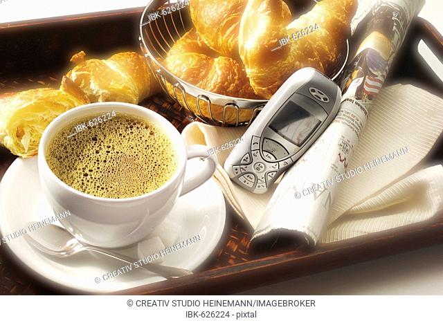 Breakfast platter with croissants, a cup of coffee, mobile phone and newspaper financial section