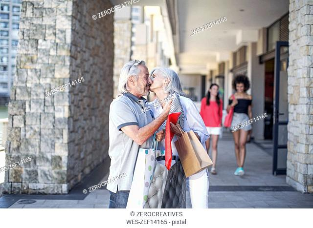 Senior couple taking a city break, going on a shopping spree