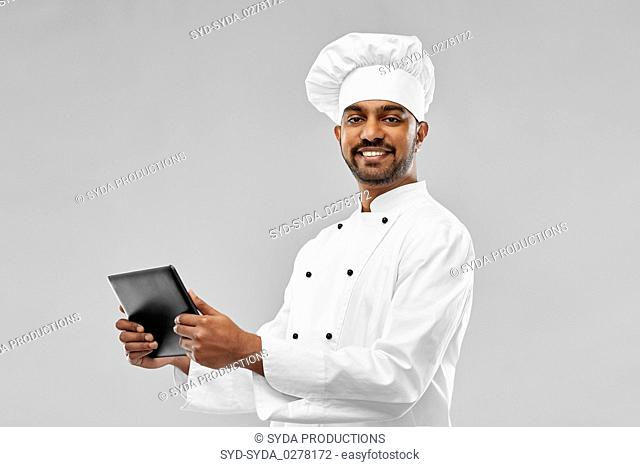 happy male indian chef with tablet computer