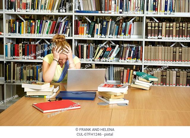 Despairing young woman in library