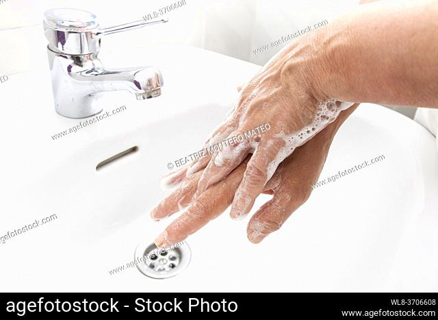 Woman washing her hands with soap and disinfecting them for Coronavirus disease