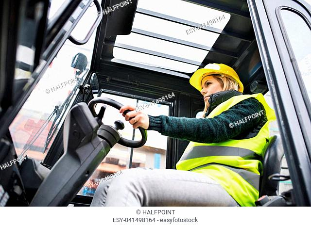 Female forklift truck driver in an industrial area. A woman sitting in the fork lift outside a warehouse