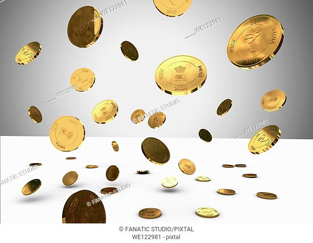 Falling gold Indian coins over gray background