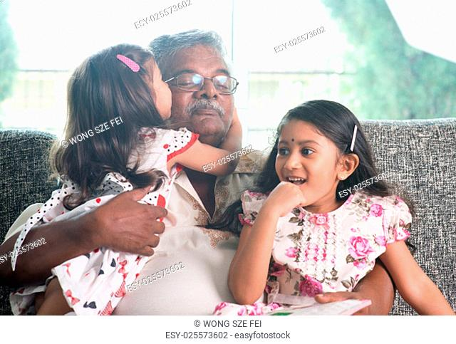 Portrait of happy Indian family at home. Grandchild kissing grandparent. Grandfather and granddaughters. Asian people living lifestyle