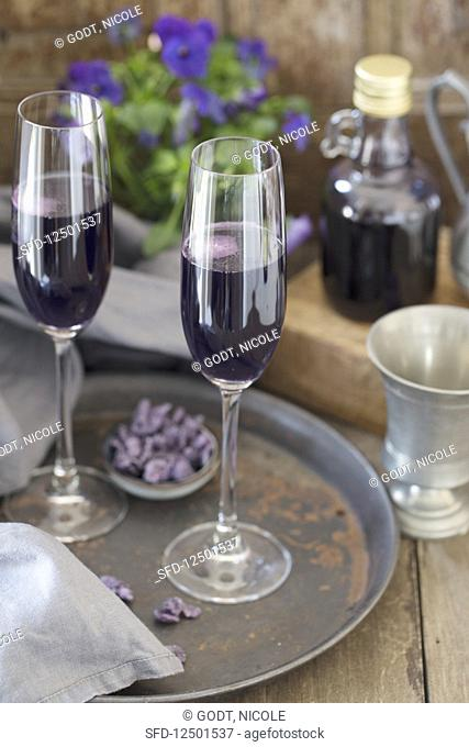 Two glasses of champagne with violet syrup from Toulouse on a tray