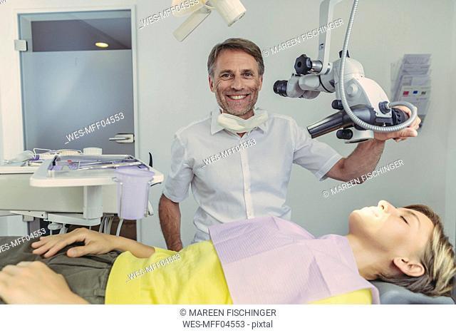 Dentist examining his patient, using dental microscope