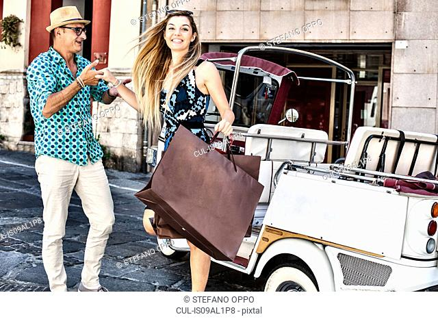 Taxi driver giving helping hand to young woman stepping from taxi, Cagliari, Sardinia, Italy