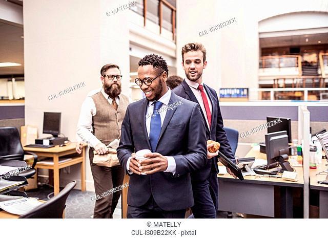 Businessmen walking through office with takeaway coffee