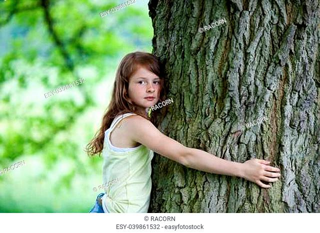 Portrait of pre adolescent girl embracing tree in park