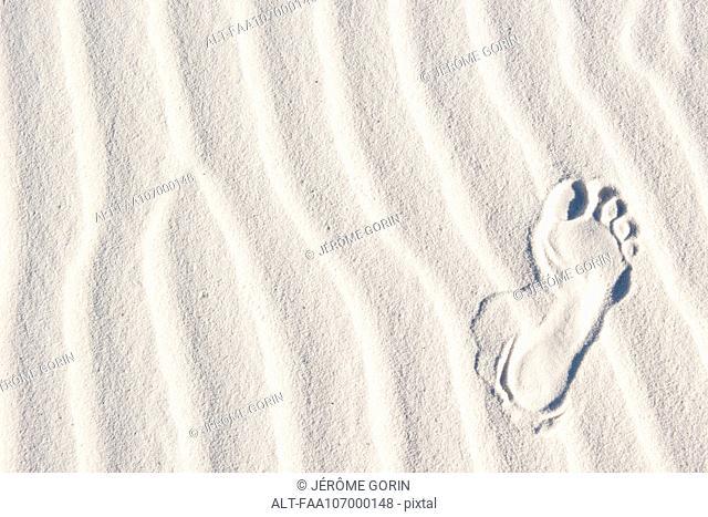Footprint in white sand