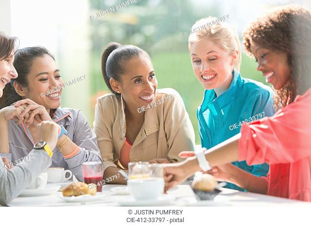 Women talking and looking at smart watch at cafe table post workout