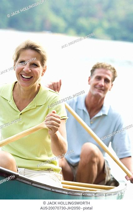 Mature couple rowing a boat and smiling