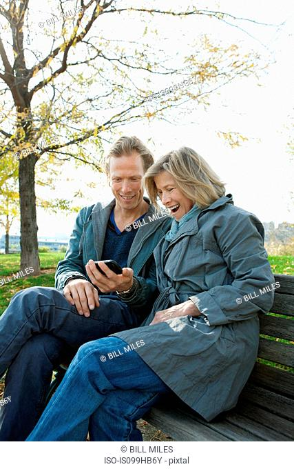 Mother and adult son on park bench looking at smartphone