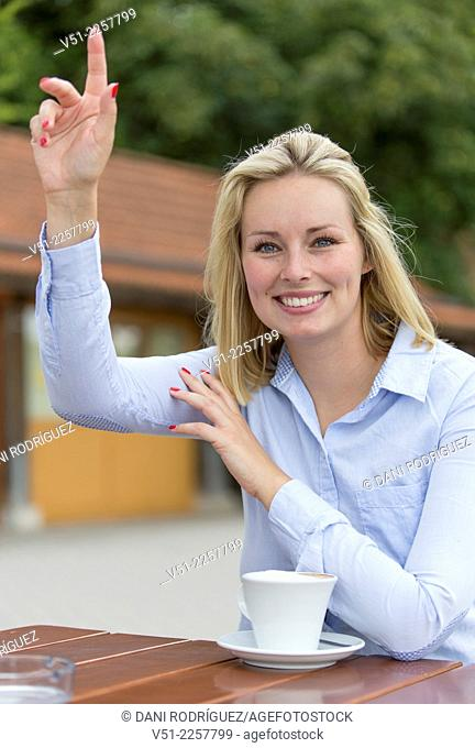 Woman in Cafe waving or asking for the bill