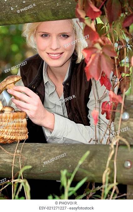 beautiful woman gathering mushrooms in the park