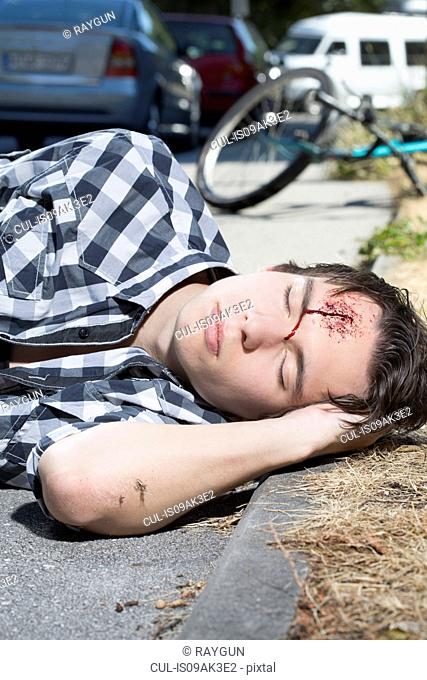 Young man lying on roadside with bleeding forehead