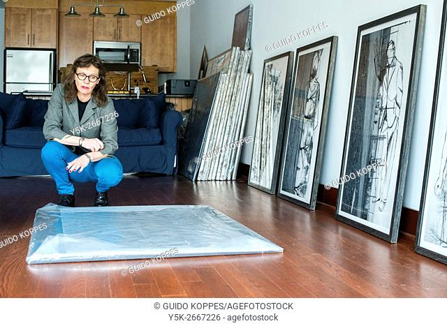 Peekskill, New York, USA. Female artist, Melinda Hunt, showing the artwork on her Hart Island Project, while giving an interview inside her studio
