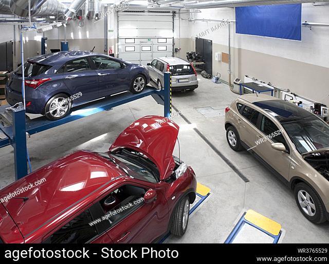 Cars in a large repair workshop or garage