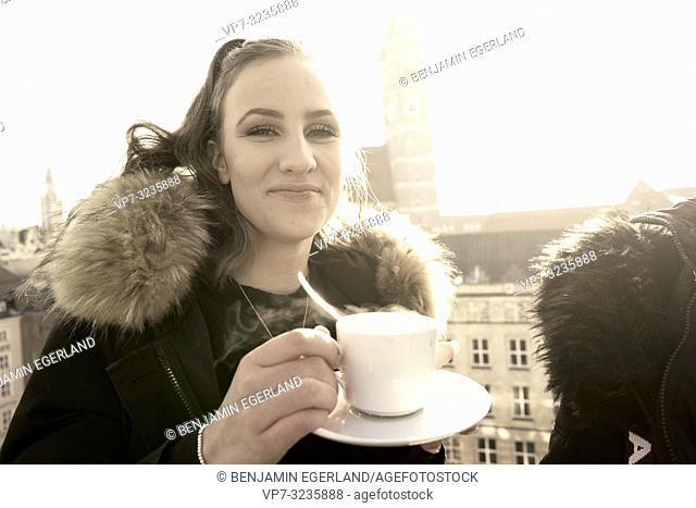 young woman with warm coffee cup outdoors next to Marienkirche, Frauenkirche, in city Munich, Germany