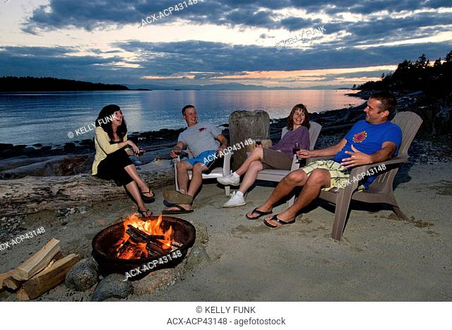 After a beautiful summer day, friends relax around the fire near Sechelt, British Columbia, Sunshine coast, Vancouver coast and mountain region, Canada