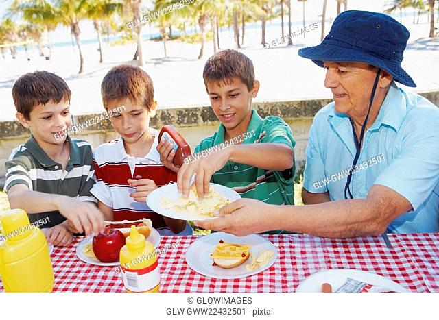 Senior man giving potato chips to his grandsons