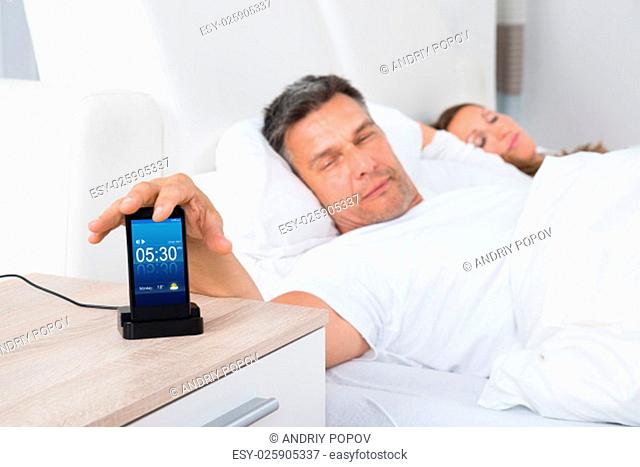 Man On Bed Snoozing Alarm Clock On Cell Phone Screen While Sleeping